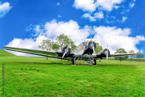 Big propeller airplane on green field in summer under blue cloudy sky.