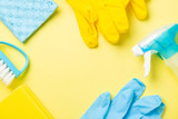 Cleaning concept - blue and yellow cleaning supplies, gloves, bottles, copy space - 242477793