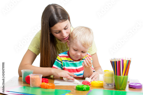 Leinwanddruck Bild Young woman playing with her boy with plasticine isolated on white background