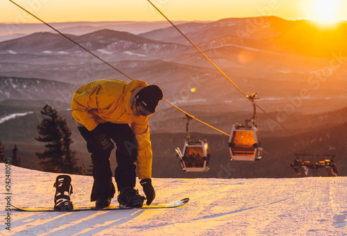 the guy comes on a snowboard at sunset - 242480519