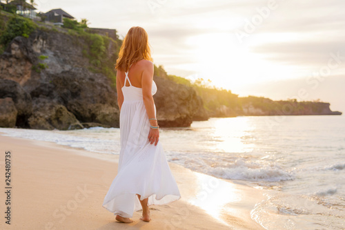 Relaxed woman in white dress walking on the beach in evening