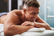 Quadro Handsome young man with closed eyes lying on massage table
