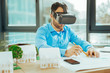 Attentive engineer smiling while working with virtual reality glasses