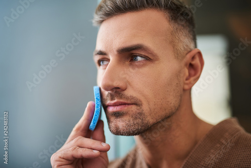 Handsome young man using blue sponge at home bathroom