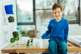 Cheerful boy sitting on the table and playing with miniature houses - 242483581