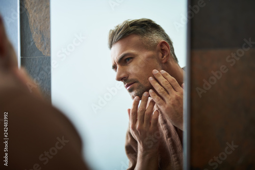 Handsome unshaven man looking in the mirror at home bathroom