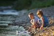 Leinwanddruck Bild - Two cute blond children, boy and girl on river bank sending in water white paper boats on bright summer blurred blue background. Joys and games of happy childhood and outdoors activities concept.