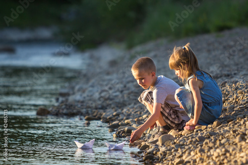 Leinwanddruck Bild Two cute blond children, boy and girl on river bank sending in water white paper boats on bright summer blurred blue background. Joys and games of happy childhood and outdoors activities concept.