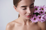 Attractive young woman keeping beautiful pink flowers on naked shoulder - 242486135