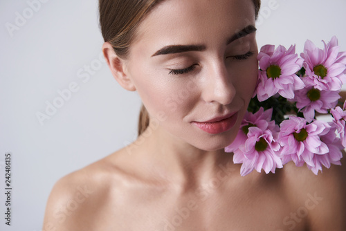 Attractive young woman keeping beautiful pink flowers on naked shoulder