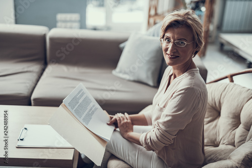 Positive psychologist smiling and holding the documents