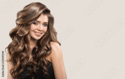Leinwanddruck Bild Portrait of beautiful cute woman with curly brown long hair. Gray background.