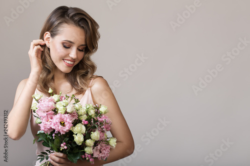 Leinwanddruck Bild Portrait of beautiful smiling woman. Holding bouquet in hands.
