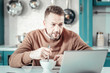 Attentive bearded man eating tasty porridge at home