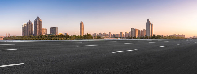 empty asphalt road and modern buildings in Zhengzhou east new district at twilight © 腾龙 郭