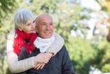 Fototapeta Miasto - Bella coppia di anziani si abbraccia affettuosamente su sfondo parco  © alex.pin