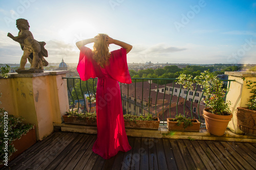 Woman standing on balcony overlooking Rome early in the morning