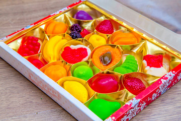 box of fruit jelly candies on wooden background