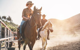 Real people riding horses inside corral - 242515547