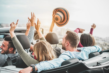 Happy friends with hands up having fun in convertible car on summer vacation