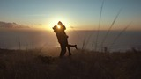 Loving couple on mountain peak at sunset - 242525172