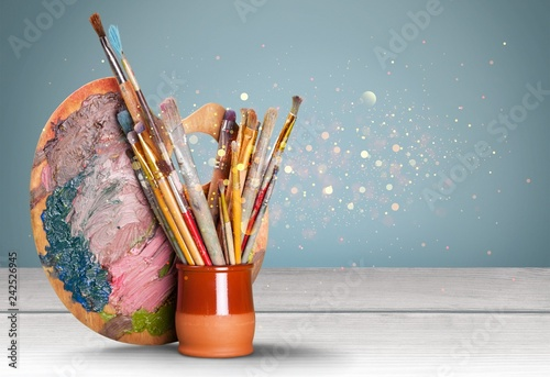 Wooden art palette with blobs of paint and a brushes on white
