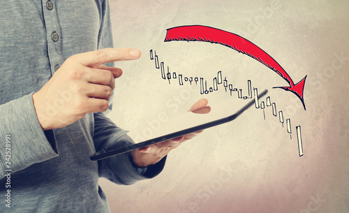 Market down trend chart with man holding a tablet computer