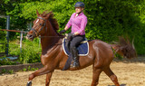 Young woman horseback riding in paddock - 242530133