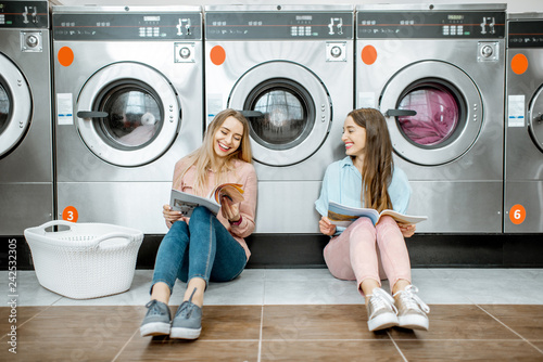 Two cheerful girlfriends having fun together while waiting for the clothes washing in the self-service laundry