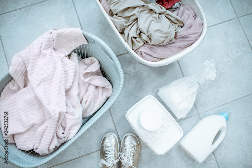 Dirty clothes in the baskets with detergents on the floor, view from above