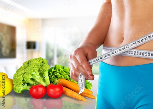 Leinwanddruck Bild Slim young woman measuring her thin waist with a tape measure