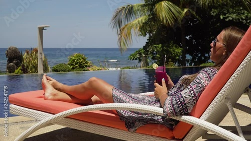 Beautiful young girl with glass of cocktail relaxing near swimming pool. Girl in sunglasses with cocktail in seafront near the bassin amongst the palm trees on the background of the sea. Travel