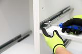 Robotnik wkręca śrubę w prowadnicy mebli. - 242549779