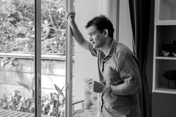 black and white picture,Middle-aged Asian man, sipping coffee and using ideas, he is stressed