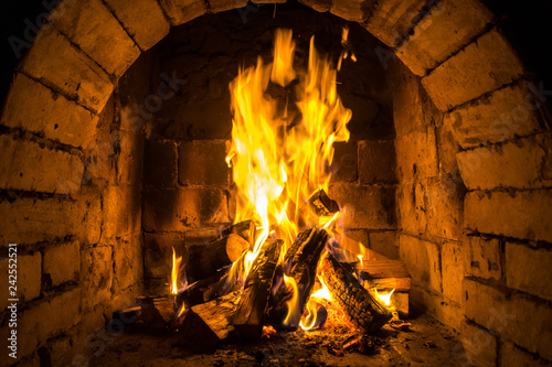 Wood burning in a cozy fireplace at home, keep warm - 242552521