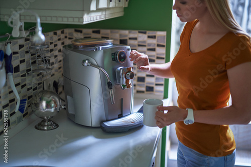 Beautiful young lady making coffee for breakfast at home