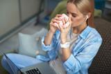 Beautiful blond girl enjoying hot drink while working on laptop - 242556583
