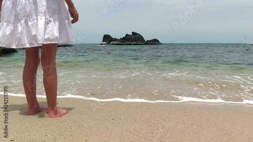 young girl at the beach just getting her feet wet on Koh Samui Island, Thailand