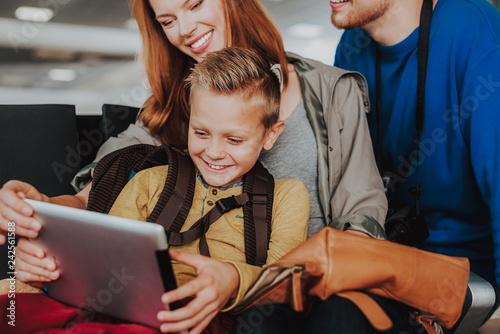 Leinwandbild Motiv Happy kid is enjoying time with parents and laptop