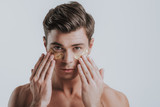 Careful young man placing eye patches on his face - 242565187