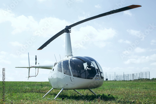 Small light helicopter parked on grass airport. Most popular light helicopters with twin blades and a single engine