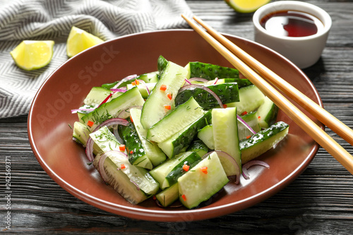 Plate with delicious cucumber salad on wooden table - 242569371