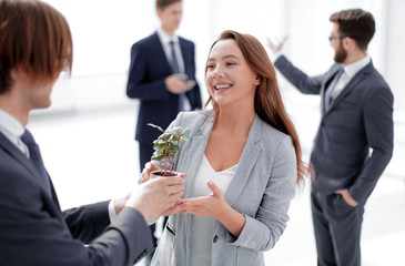 businessman and businesswoman holding a pot with sprouts