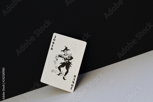 Unpredictable joker as symbol of opposites, contradictions of human nature. Black joker on contrasting white and black background. - 242580180