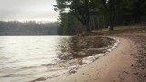 Gentle water lapping onto sandy shore at public beach - 242597594