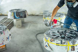 Automobile disc restoring. Painter painting light alloy wheel with spray - 242597967