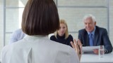 Tracking of woman in glasses talking about her skills and professional experience during panel job interview. Bearded businessman, blond businesswoman and elderly manager talking and making notes - 242606395