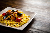Roasted meat, pasta and vegetables on wooden background