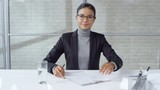 POV shot of cheerful businesswoman in glasses and formalwear talking and taking CV on clipboard from job candidate during interview - 242613576