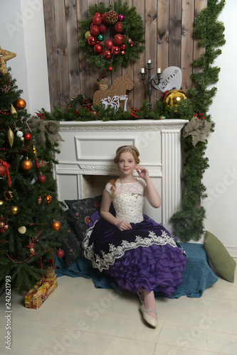 Girl in purple dress at christmas. Dream, hands.